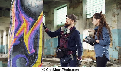 Attractive bearded guy graffiti artist is talking to his...