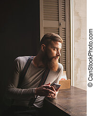 Attractive bearded guy is messaging on telephone
