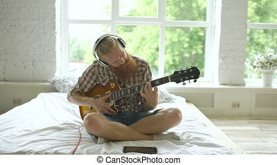Attractive bearded man in headphones sitting on bed learning...