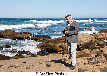 Attractive bearded man on the beach with phone and tablet