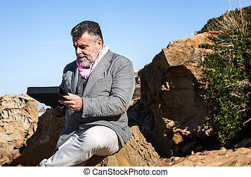 Attractive bearded man on the beach with tablet