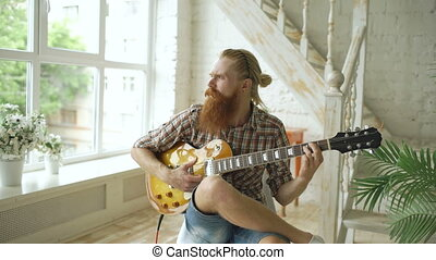 Attractive bearded man sitting on chair learning to play...