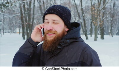 Attractive bearded man talking on the phone