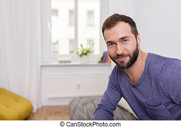 Attractive bearded man with a friendly smile sitting on a...