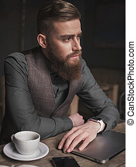 Attractive bearded old-fashioned man with modern technology