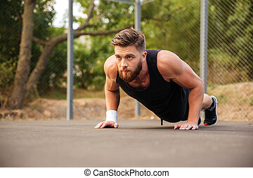 Attractive bearded sportsman doing push-ups outdoors