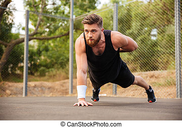 Attractive bearded sportsman doing push-ups with one hand outdoors