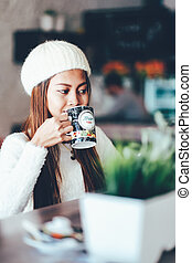 Attractive beautiful girl enjoying drinking tea in a cafe