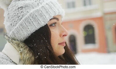 Attractive beautiful lady posing and flirting on camera over snowy city background