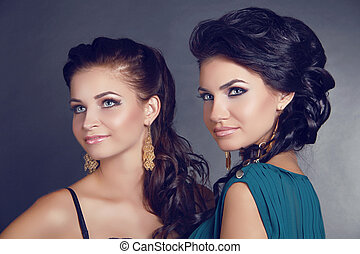 Attractive beautiful two women portrait looking away on gray background