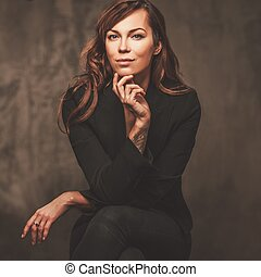 Attractive beautiful woman in black sitting on chair isolated on gray background.