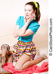attractive beautiful young girl pinup in a striped skirt and blue shirt sewing& looking at camera portrait
