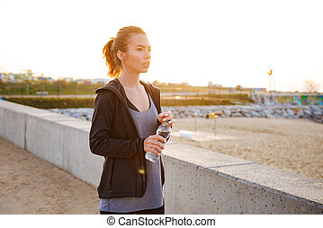 Attractive beautiful young sports woman drinking water