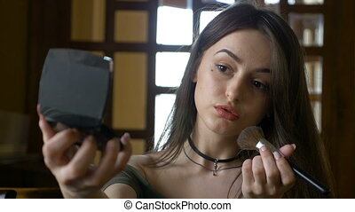 Attractive beautiful young woman applying blush makeup  on her cheeks