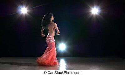 Attractive belly dance woman bellydancer dancing on black, back light, slow motion