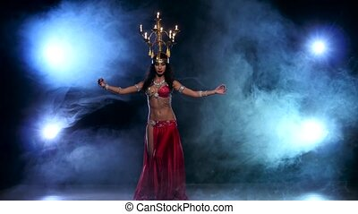 Attractive belly dancer continue dancing with candles on her head, black, smoke