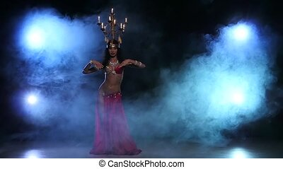 Attractive belly dancer continue dancing with candles on her head, black, smoke, slow motion