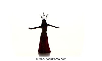Attractive belly dancer dancing with candles on her head, shaking her hips, silhouette, on white