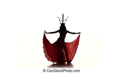 Attractive belly dancer dancing with candles on her head, silhouette, on white