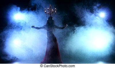 Attractive belly dancer dancing with candles on her head, black, smoke, silhouette
