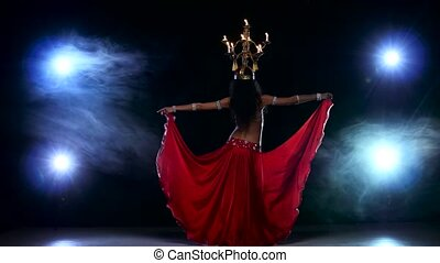 Attractive belly dancer girl continue dancing with candles on her head, black, smoke