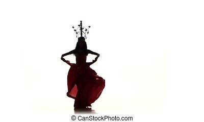 Attractive belly dancer girl dancing with candles on her head, silhouette, on white