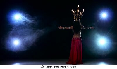 Attractive belly dancer girl go on dancing with candles, her head, black, smoke