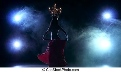 Attractive belly dancer go on dancing with candles, her head, black, smoke, silhouette