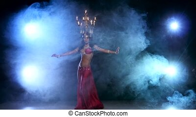 Attractive belly dancer starts dancing with candles on her head, black, smoke