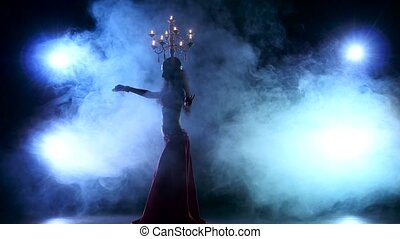 Attractive belly dancer starts dancing with candles on her head, black, smoke, silhouette