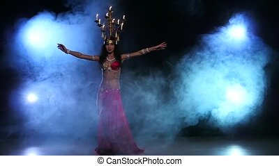 Attractive belly dancer starts dancing with candles on her head, black, smoke, slow motion