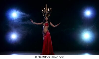 Attractive belly dancer woman dancing with candles on her head, black, smoke