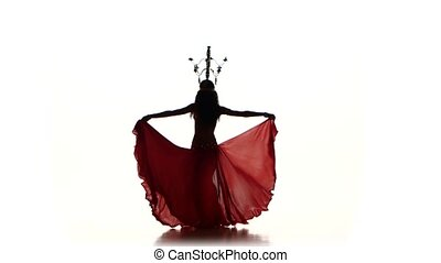 Attractive belly dancer woman dancing with candles on her head, silhouette, on white