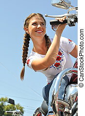 attractive biker woman sitting on her motorcycle