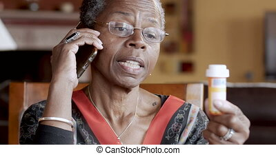 Attractive black senior woman refilling her prescription on a smart phone