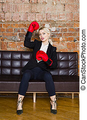 Attractive blond businesswoman with boxing gloves ready for a fight in front of an apartment. Business concept.
