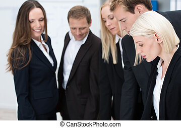 Attractive blond businesswoman with her team