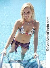 blond female model having fun in the pool