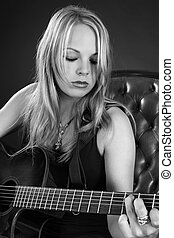 Attractive blond female playing guitar