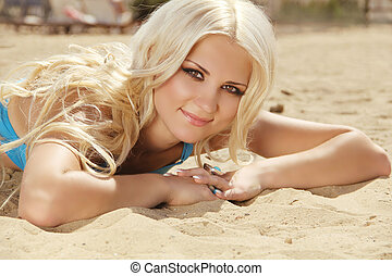 Attractive blond girl sunbathing on beach