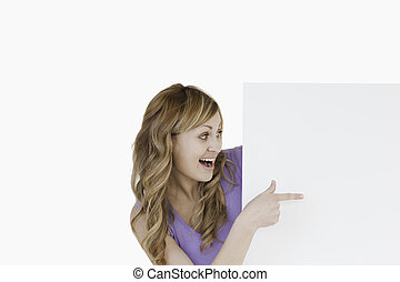 Attractive blond-haired woman holding a white board
