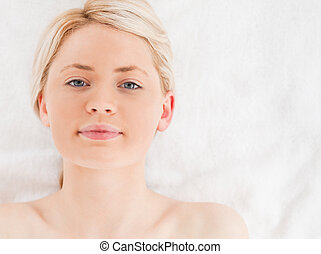 Attractive blond-haired woman looking at the camera while lying down in a Spa centre