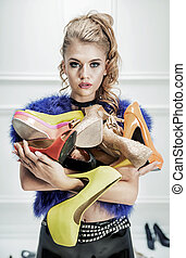 Attractive blond lady holding a bunch of shoes