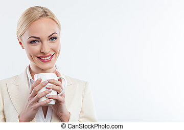 Attractive blond lady is drinking hot coffee