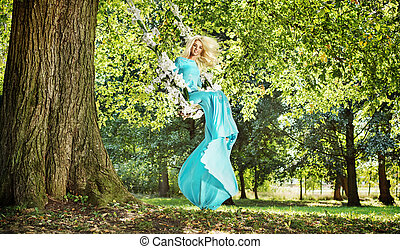 Attractive blond lady on a flower seesaw in a park
