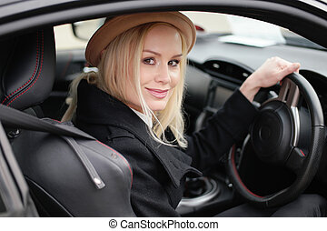 Attractive blond woman at the wheel of her car