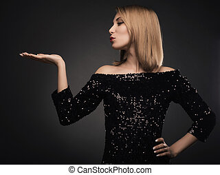 Attractive blond woman blowing kiss against grey background.