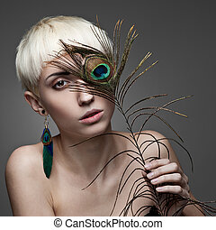 attractive blond woman holding peacock feather