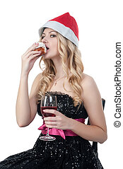 Attractive blond woman in christmas hat eats cake