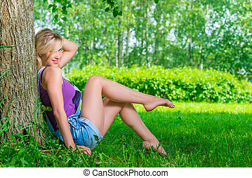 attractive blond woman in the park on a summer day resting